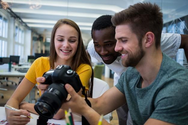 Projektant graficzny pokazujący obraz z kolegami w aparacie