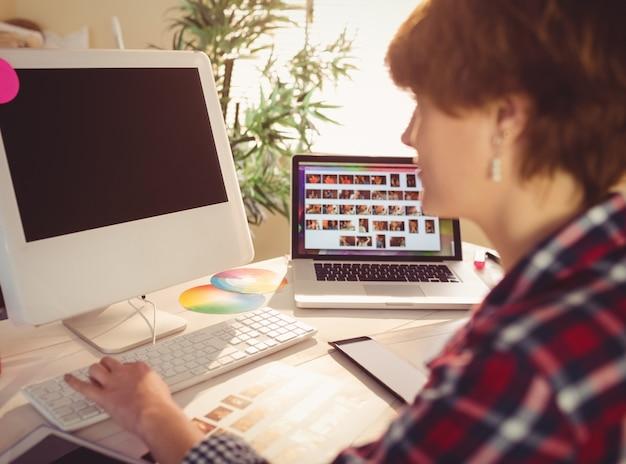Projektant graficzny pracuje na swoim komputerze