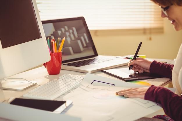 Projektant graficzny pracuje przy biurkiem