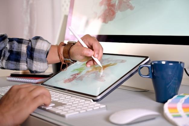 Projektant graficzny pracuje z cyfrową rysunkową pastylką przy pracownianym miejscem pracy.