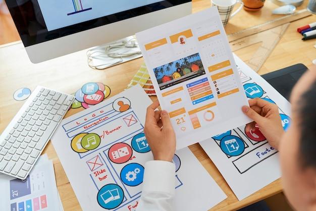 Projektant interfejsu użytkownika trzymający stronę z układem nowej aplikacji mobilnej mediów społecznościowych