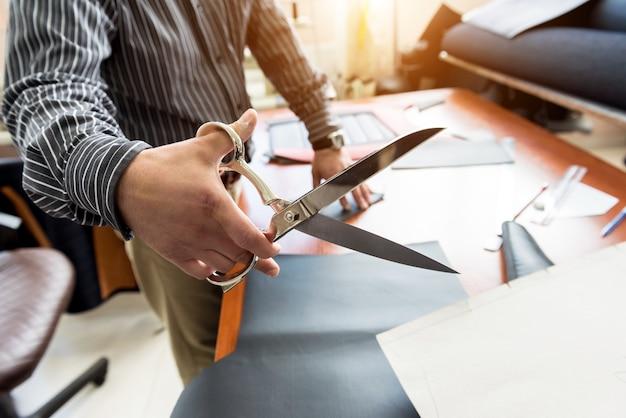 Projektant krawiecki szyje pokrowce na siedzenia. mężczyzna używa nożyczek do swojej pracy. robocza szmatka krawiecka. fabryka tekstyliów.