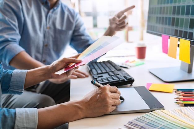 Projektant kreatywność graficzna współpracujący z kolorem przy użyciu tabletu graficznego i rysika na biurku z kolegą