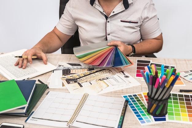 Projektant kreatywny pracujący z planem szkicu i próbnikiem kolorów