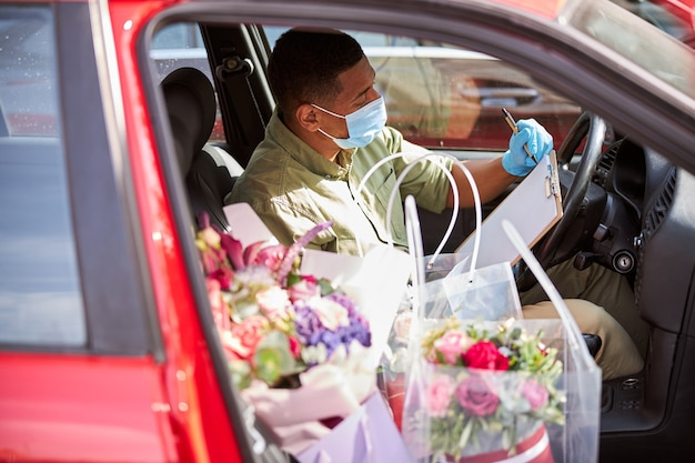 Projektant kwiatów w szpitalnej masce siedzący za kierownicą z papierowym schowkiem i bukietami obok niego