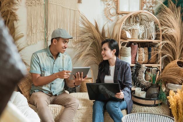 Projektant, mężczyzna i kobieta-przedsiębiorca, opowiadają o sprzedaży rękodzieła za pomocą tabletu i laptopa przez wiele rzemieślników