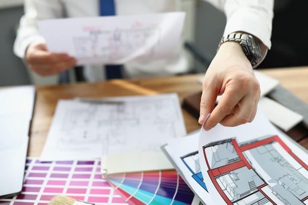 Projektant mężczyzna siedzi przy stole i trzyma projekt mieszkania w jego rękach