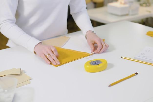 Projektant mody lub krawiecka tkanina do cięcia podczas pracy z rysunkiem szkicu i materiału na stole roboczym