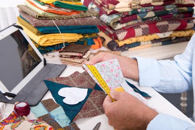Projektant mody mężczyzna pomiaru kawałka tkaniny
