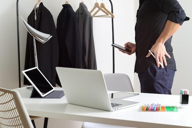Projektant mody opowiada telefon komórkowego i używa laptop z cyfrowym pastylka komputerem w nowożytnym studiu