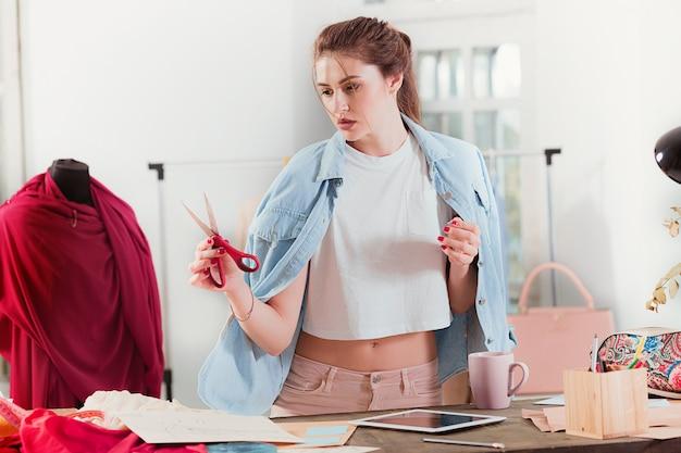 Projektant mody pracuje w studiu siedzącym na biurku