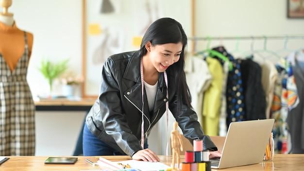 Projektant mody pracuje z laptopem.