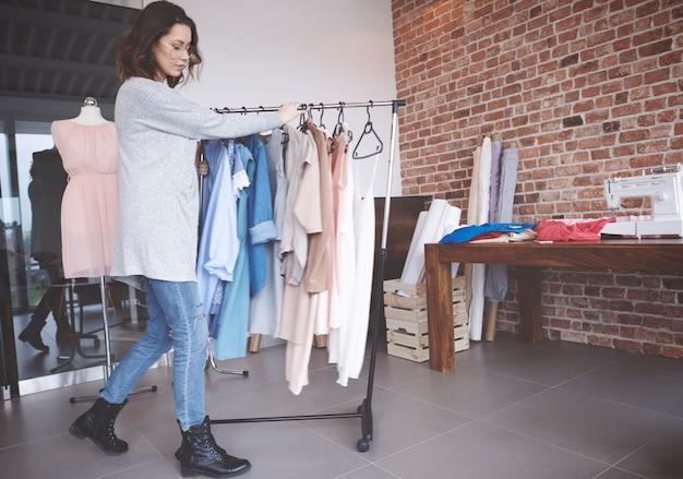 Projektant mody spacerujący z wieszakiem na ubrania