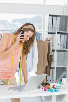 Projektant mody używa laptop i telefon komórkowego w studiu