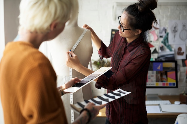 Projektant mody za pomocą taśmy pomiarowej na manequin