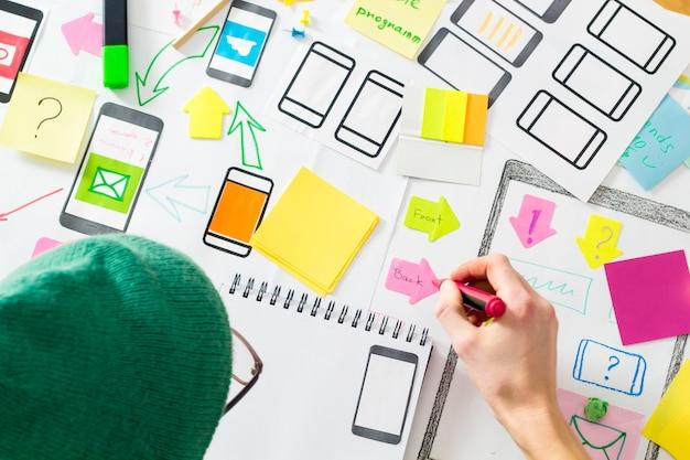 Projektant na komputerze tworzy aplikacje internetowe na telefony komórkowe. doświadczony użytkownik.