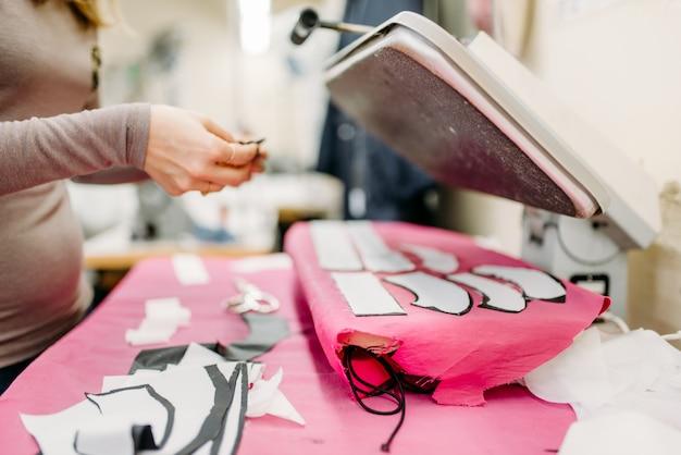 Projektant odzieży pracuje z wykrojami sukienek na prasie parowej, produkuje w szwalni. krawiectwo lub krawiectwo