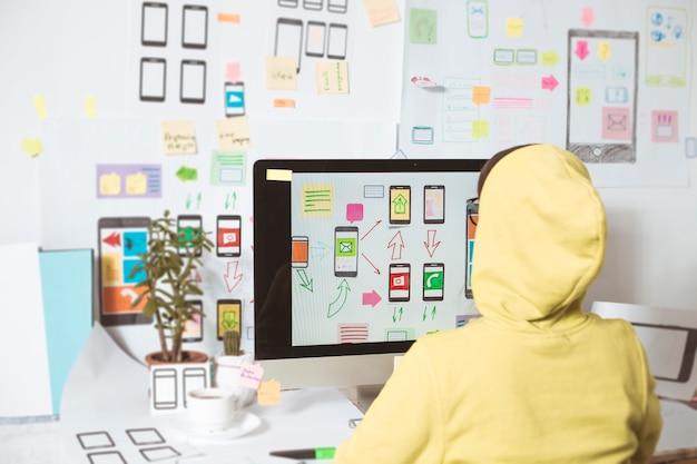 Projektant opracowuje aplikacje na telefony komórkowe.