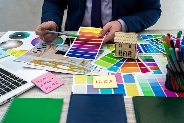 Projektant opracowuje szkic ilustracji wnętrza z kolorystyką materiału na stole, biurowym miejscu pracy. pulpit architekta i projektanta wnętrz z próbkami wyposażenia i materiałów