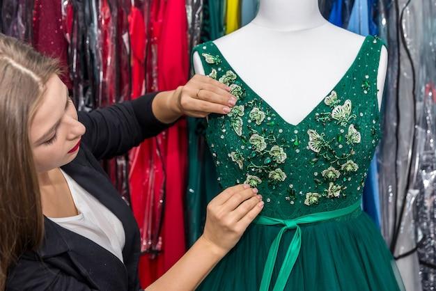 Projektant pracujący z suknią wieczorową na manekinie