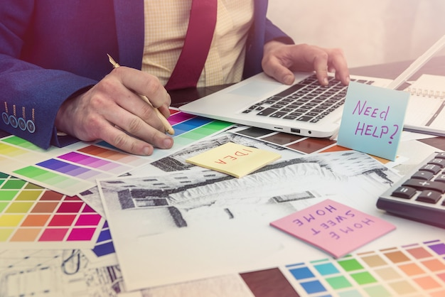 Projektant pracuje w biurze z domowym kreatywnym szkicem i próbką kolorów do nowoczesnej renowacji. projekt architekta