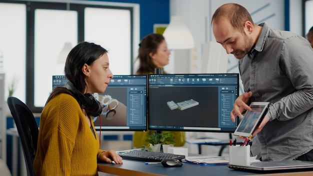 Projektant przemysłowy trzymający tablet rozmawiający z kobietą inżynierem podczas pracy w programie cad
