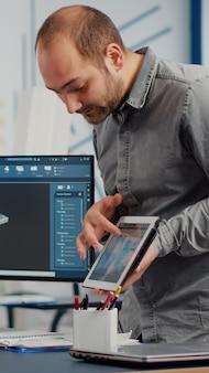 Projektant przemysłowy trzymający tablet rozmawiający z kobietą inżynierem podczas pracy w projektowaniu programu cad...