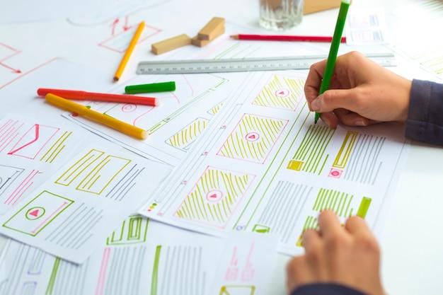 Projektant rysuje szkice strony internetowej.