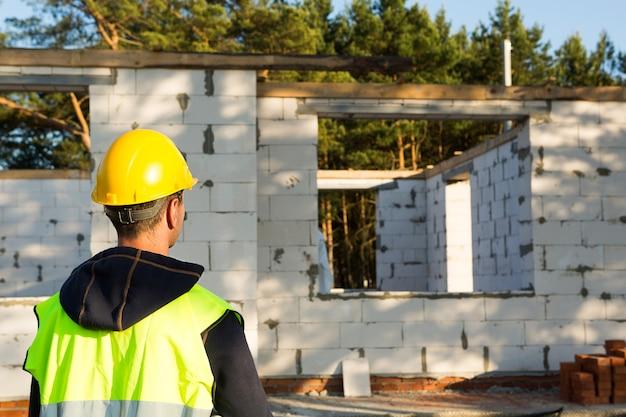 Projektant stoi w pobliżu placu budowy domu, którego ściany wykonane są z pustaka betonowego i cegły. pracownik budowlany w ochronnym żółtym kasku i kamizelce odblaskowej.