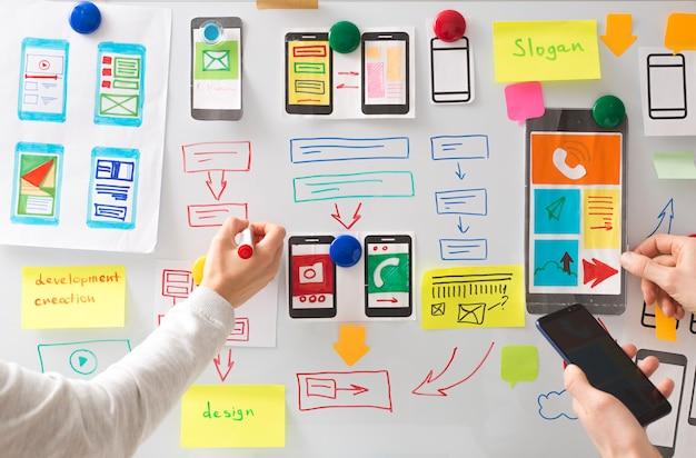 Projektant stron internetowych opracowuje interfejs użytkownika do aplikacji na telefony komórkowe.
