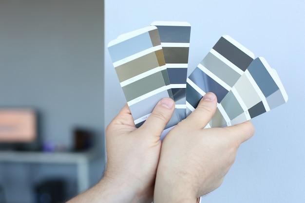 Projektant trzyma w ręku przewodnik po kolorach.