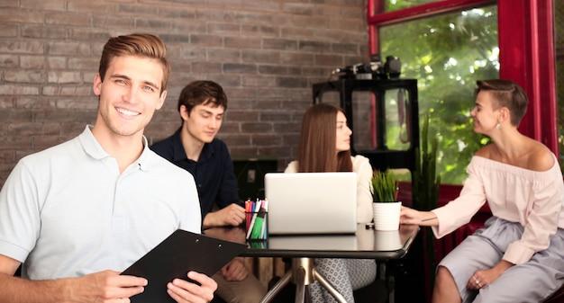 Projektant w swobodnym stroju siedzi, patrzy w kamerę i uśmiecha się, jego koledzy pracują w tle.