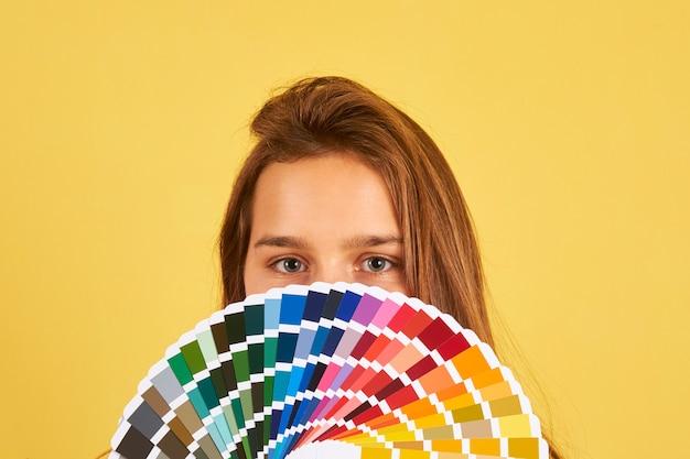 Projektant wnętrz kobieta trzyma paletę kolorów przewodnik na żółtym tle