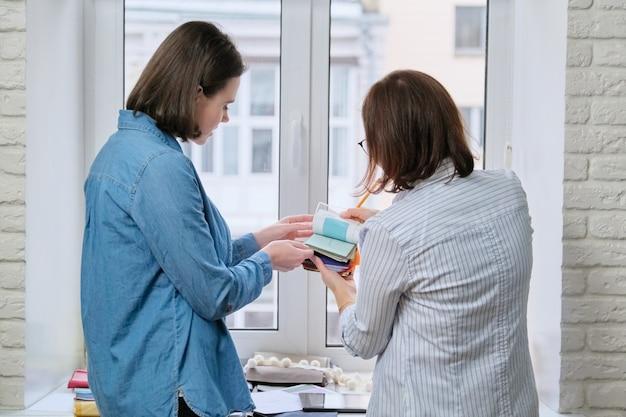 Projektant wnętrz pokazuje kobiece klientki próbki tkanin na zasłony i tapicerkę, nowy projekt mieszkaniowy