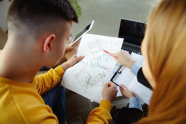Projektant wnętrz pracujący z młodą parą. urocza rodzina i profesjonalny projektant lub architekt omawiający koncepcję przyszłego wnętrza, pracujący z paletą kolorów, rysunkami pokoi w nowoczesnym biurze.