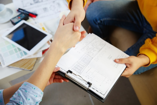 Projektant wnętrz pracujący z młodą parą.