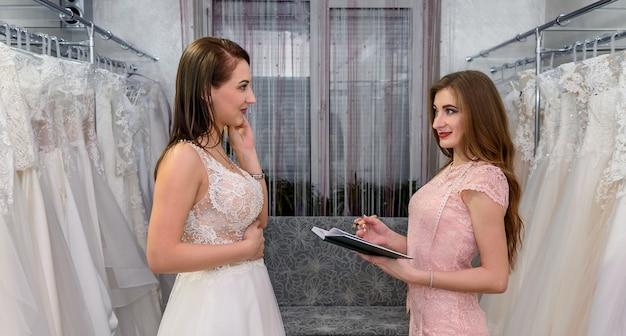 Projektant z notatnikiem i klientką w sklepie ślubnym