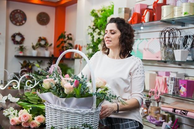 Projektantka kwiaciarni zbierająca kwiaty, aby zrobić bukiet w białym koszu. sklep kwiatowy przygotowujący prezenty na wakacje lub do dekoracji. koncepcja dostawy kwiatów.