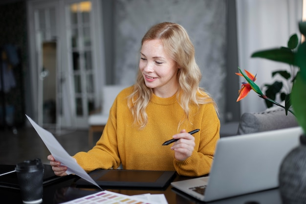 Projektantka logo pracująca na swoim tablecie podłączonym do laptopa