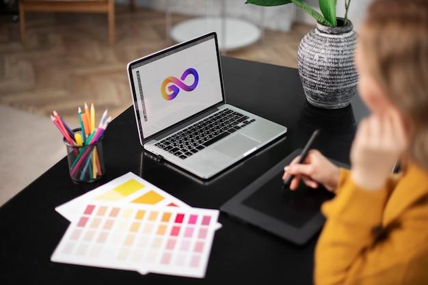 Projektantka logo pracująca na tablecie podłączonym do laptopa