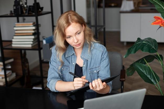 Projektantka logo pracująca w swoim biurze na tablecie graficznym