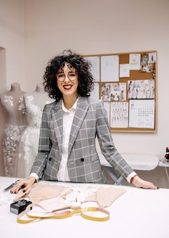 Projektantka mody kobieta w swoim studio uśmiechnięta, pracująca nad nową kolekcją sukien ślubnych