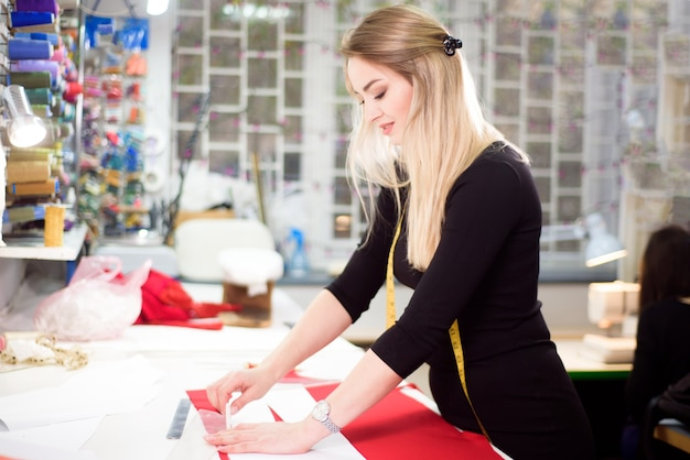 Projektantka mody krawiecka lub krawiecka w pracowni projektowej projektującej ubrania z nowej kolekcji.