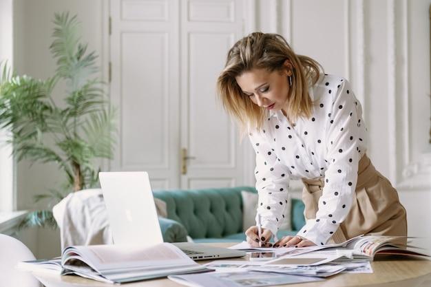 Projektantka mody stylistka pracująca nad nowym projektem w studio, korzystająca z laptopa, czasopism, szkiców ... freelancerka