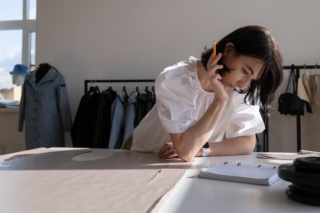 Projektantka odzieży damskiej w studiu zamyślona nad wymiarami tkanin do przyszłej kolekcji w pracy