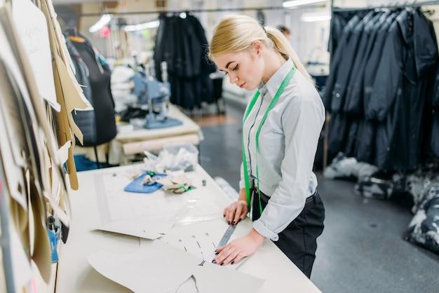 Projektantka odzieży mierzy wzór, manufaktura w szwalni. pomiar krzywizny sukni, krawcowa, krawiectwo lub krawiectwo