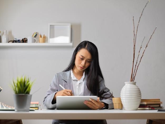 Projektantka pracująca z cyfrowym tabletem i materiałami eksploatacyjnymi