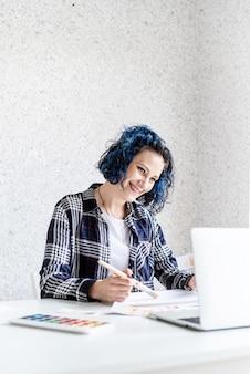 Projektantka pracująca z paletami kolorów i laptopem w swoim studio artystycznym