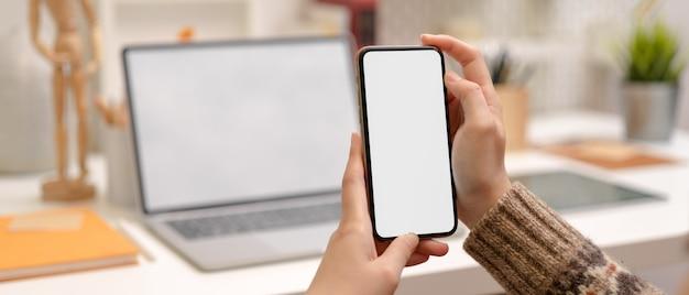 Projektantka robi sobie przerwę z makietą smartfona, siedząc przy stole roboczym