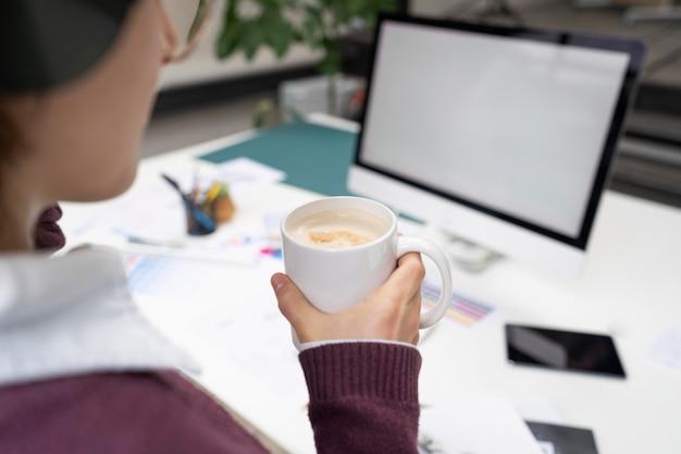 Projektantka trzymająca kubek z kawą